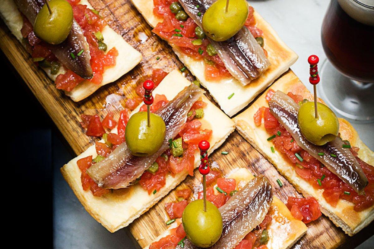Cocas con sardinas ahumadas, tartar de tomate y encurtidos